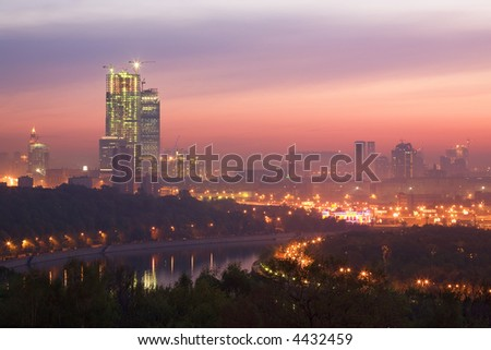 Sunrise, game of paints in the sky, above the river - not completed building with fires - stock photo