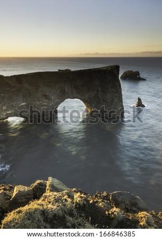 Sunrise highlights Iceland's Dyrholaey arch  - stock photo