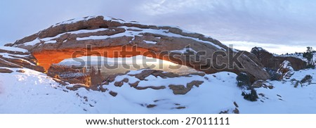 Sunrise illumination of snow covered Mesa Arch. - stock photo