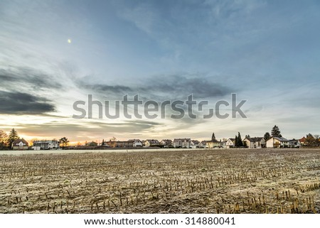sunrise in a suburb of Munich with Chinook winds and houses at the horizon - stock photo