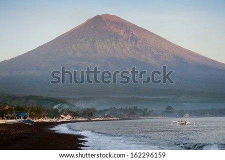 Sunrise in Amed, Bali, Indonesia. The active volcano Gunung Agung looms over the black sand beach of Jemeluk in the area known as Amed in the eastern shore of the tropical island of Bali. - stock photo