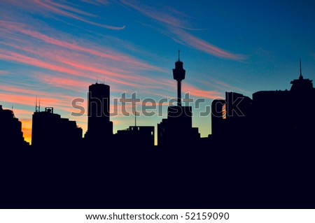 Sunrise in Sydney with Sydney tower and skyscrapers in silhouette.