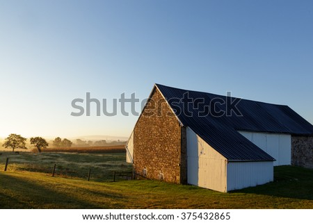 Sunrise in the country with an old barn in the foreground