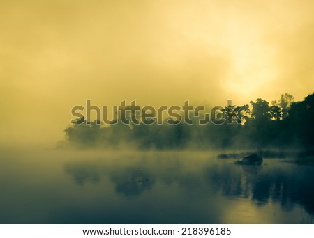 Sunrise in the Mist on lake and reflection on the water. - stock photo
