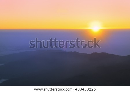 Sunrise in the mountains. View with rising sun and silhouettes of mountains from peak of Teide Tenerife, Canary islands, Spain