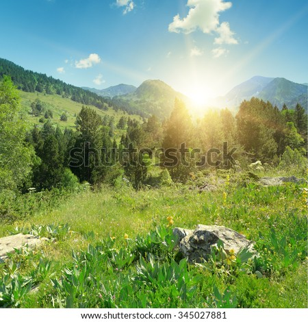 Sunrise in the mountains with rocks in foreground - stock photo