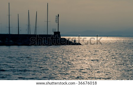 Sunrise in the port (Port landscape with fishermen`s silhouette on the pier in the morning) - stock photo