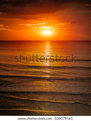 Sunrise in the sea with soft wave and cloudy - stock photo