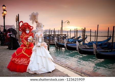 Sunrise in Venice Italy in front of Gondolas on the Grand Canal Beautiful costumed women - stock photo