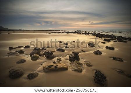 Sunrise landscape on rocky sandy beach with vibrant sky and clouds - stock photo