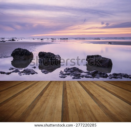 Sunrise landscape on rocky sandy beach with vibrant sky and clouds - stock photo