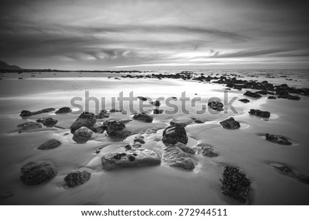 Sunrise landscape on rocky sandy beach with vibrant sky and clouds in black and white - stock photo