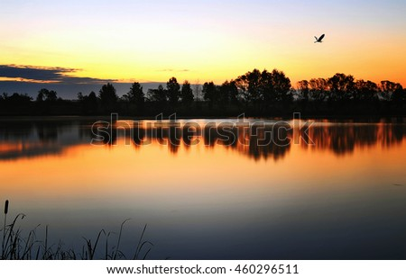 Sunrise landscape with a lake and the mist over the water - stock photo
