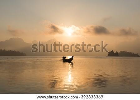Sunrise Landscape with Silhouette Boat - stock photo