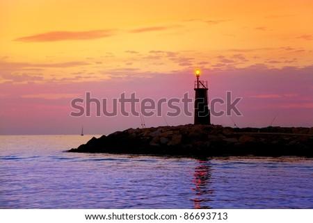 Sunrise lighthouse glowing in blue purple sea and orange sky - stock photo