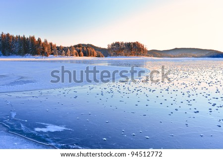 Sunrise lights in the frosted mountain lake - stock photo