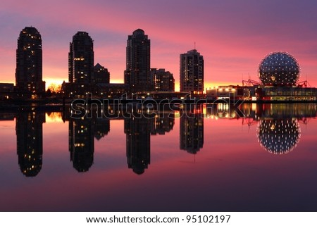 Sunrise lights up the Vancouver skyline on the edge of False Creek including condominium towers and the geodesic dome of Science World. British Columbia, Canada.