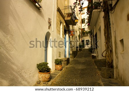 Sunrise. Narrow street in a small Mediterranean village. Cadaques, Costa Brava, Catalonia, Spain - stock photo
