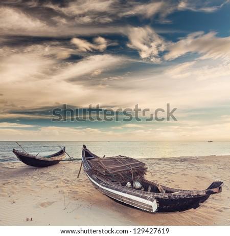 Sunrise. Old fisherman boats on the foreground - stock photo
