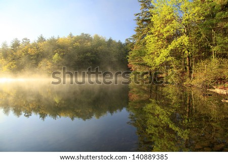 Sunrise on a Foggy Mountain Lake - stock photo