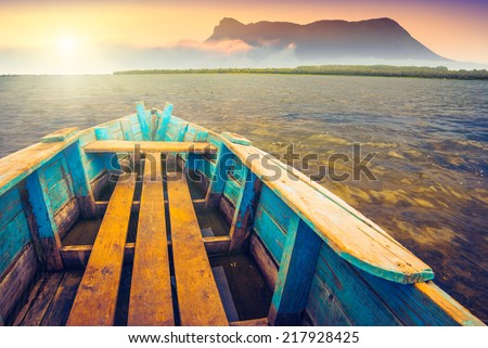 Sunrise on a mountain lake with rustic wooden boat and old foggy volcano on a skyline - stock photo