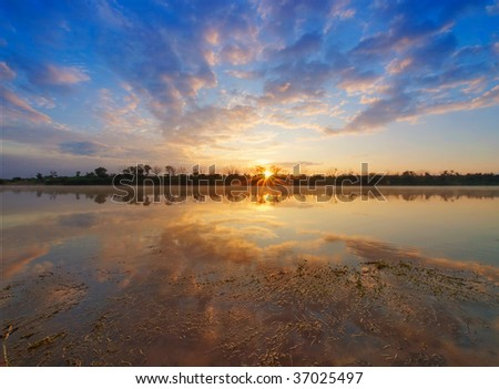 Sunrise on a river. - stock photo