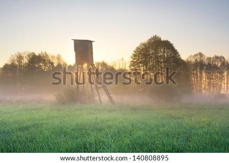 sunrise on foggy meadow with raised hide - stock photo