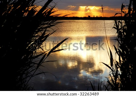 Sunrise on lake and clouds - stock photo