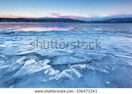 Sunrise on Payette Lake in McCall, Idaho adds a little color to an otherwise greyscale landscape. - stock photo