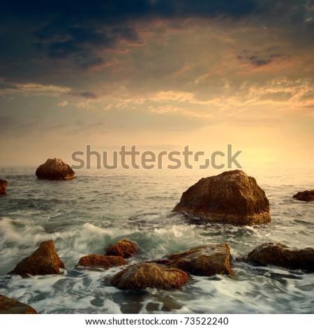 sunrise on rocky sea coast and blurred water - stock photo