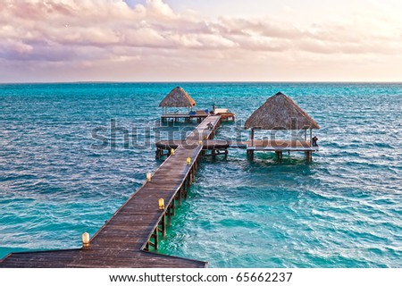 Sunrise on the Atlantic coast. As the water leaves the pier with two bungalows. Fishermen on the pier. In the sky clouds and seagulls. - stock photo