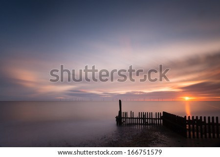 Sunrise on the beach at Caister on the Norfolk coast, looking out towards the offshore wind farm in the distance - stock photo