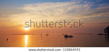 Sunrise on the Chesapeake Bay coast with crab boat and sail boats