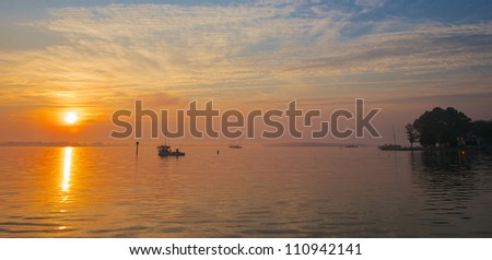 Sunrise on the Chesapeake Bay coast with crab boat and sail boats - stock photo