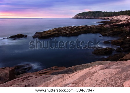 Sunrise on the coast of Maine at Acadia National Park.  The sun is rising over Otter Cliffs with a long exposure of the water.  Pink granite sits in the foreground as an accent. - stock photo