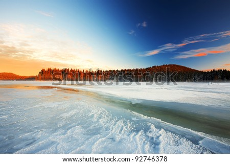 sunrise on the frost lake in wild area - stock photo