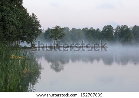 sunrise on the lake with a view of the hazy bridge - stock photo