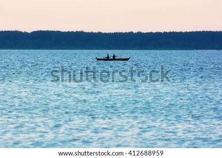 Sunrise on the lake with boat fishermen. - stock photo