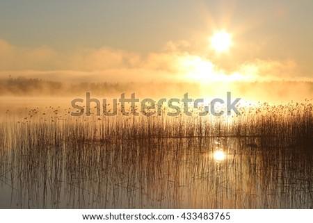Sunrise on the lake with haze. - stock photo