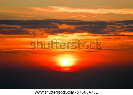 Sunrise on the mountain with orange light and clouds on sky.