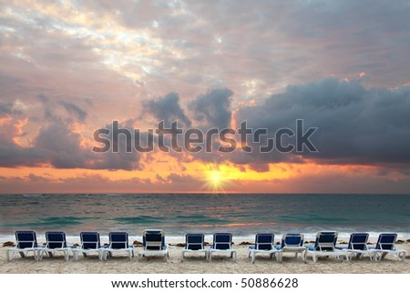 Sunrise on tropical beach resort,beach beds waiting for early bird tourists - stock photo