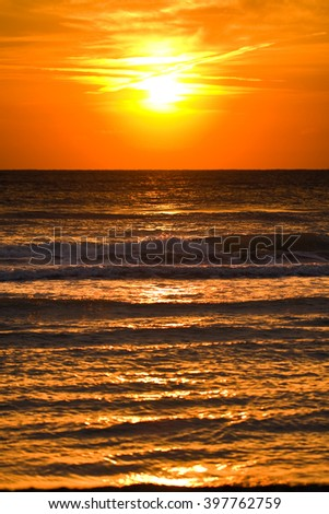 Sunrise or sunset at sea with the Sun blurred by aerial wakes   - stock photo