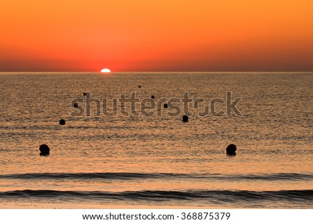 sunrise or sunset at the sea with part of the Sun into water behind horizon level and buoys to delimit path - stock photo