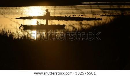 sunrise or sunset kayak fishing in beautiful landscape - stock photo