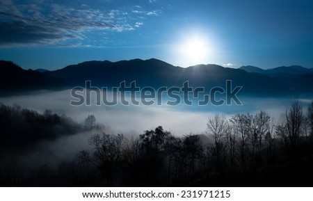 Sunrise over a curtain of mist that lies above the valley.