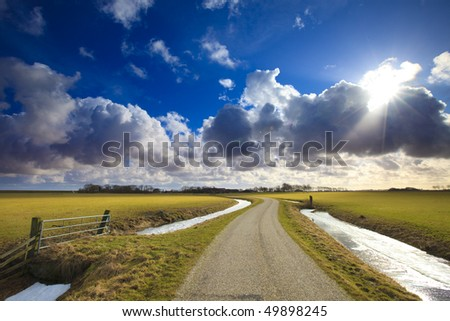 Sunrise over a flat field in Holland with a bright sky and clouds - stock photo