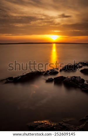 Sunrise over a lake in Sweden with a reflection of a  sunbeam in the smooth water surface - stock photo