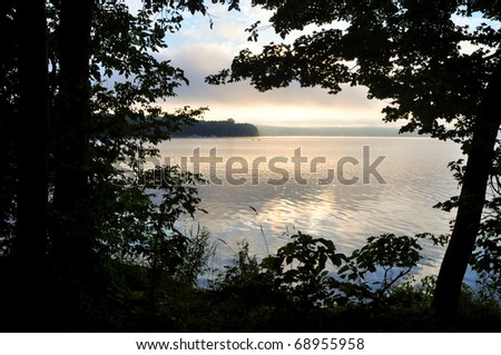 sunrise over a lake, through trees - stock photo