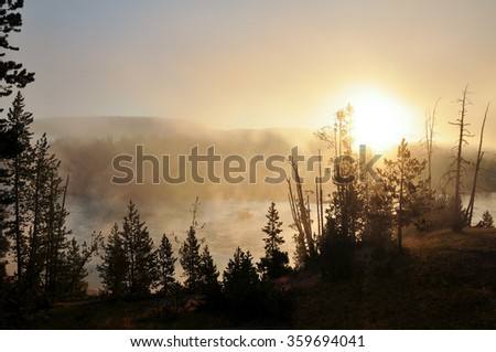 Sunrise over a misty lake in Yellowstone National Park - stock photo