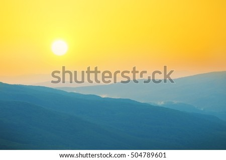 sunrise over a misty summer landscape.bright morning sun in an orange sky over a mountain landscape.the Golden glow from the rising sun in the mountains in the summer